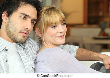 Young couple watching TV at home