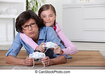 Young girl playing a video game with her grandmother