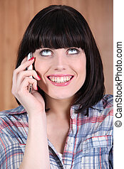 Woman with a broad grin talking on the phone