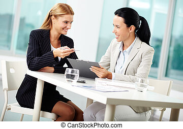 Planning work - Portrait of two young businesswomen planning...