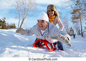 Winter happiness - Portrait of happy mature couple riding on...