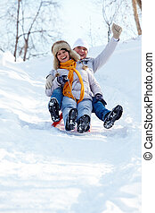 Tobogganing couple - Portrait of happy mature couple riding...