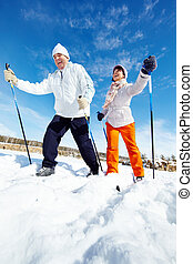 Winter sport - Portrait of happy mature couple skiing...