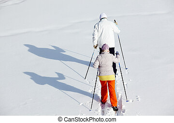 Backs of skiers - Rear view of mature couple skiing in...