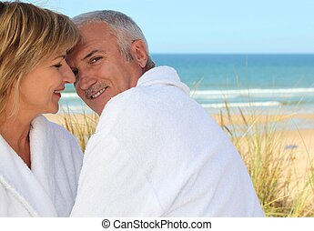 Older couple smooching in the sand dunes
