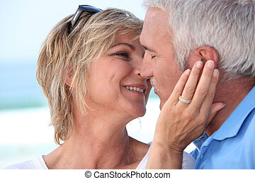 Middle aged couple kissing at the beach.