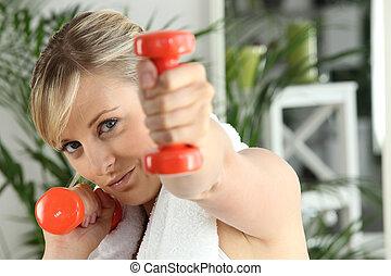 a woman lifting dumbbells