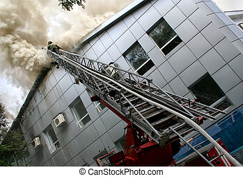 Building on fire. firefighter puts out a fire while on a...