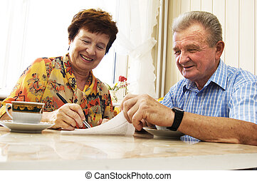 Senior couple signing document in home