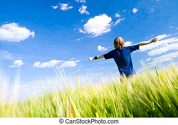 Happy man with arms up on summer field