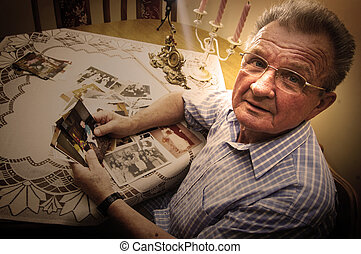 Senior man looking at old photographs Reminisce about the...