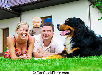 Happy family and house - Happy family in front of their...