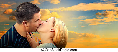 Couple kissing in romantic love scenery on sunset sky....