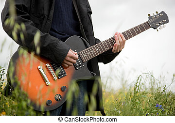 Close up of a man playing guitar outdoors