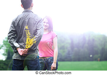 Romantic young couple - Young man just before giving flowers...
