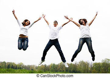 Happy friends jumping - Three happy friends jumping with...