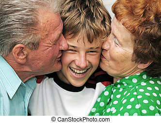 Grandparents with grandson - Grandparents kissing their...
