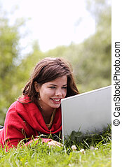 A beautiful student girl working on her laptop outdoor at sunny day