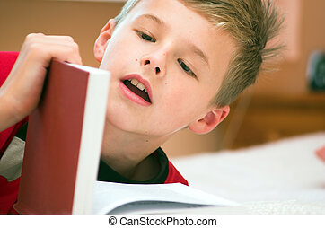 Reading book - Young boy reading book on the bed