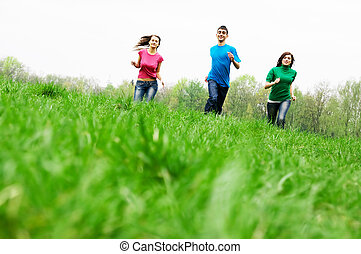 Happy friends jumping - Three happy friends having fun on...