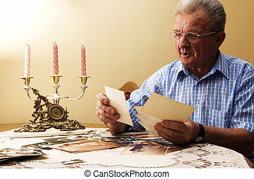 Senior man looking at old photographs. Reminisce about the...