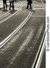 Crossing the tramlines - Pedistrians cross silvery grey...