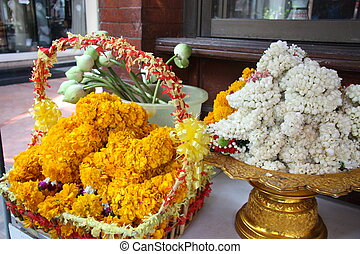 Sacrificial flowers on a golden tray and in a basket, in a...