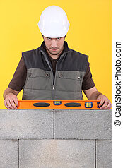 Construction worker measuring an angle with a spirit level