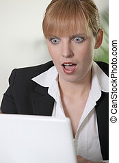 Shocked woman looking at laptop
