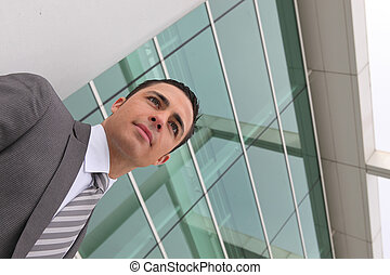Young executive standing outside a modern office building