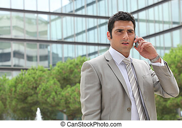 Businessman outdoors talking on phone