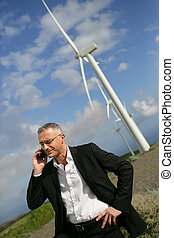 Man using his cellphone next to wind turbines