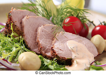 Roast pork tenderloin served with vegetables - detail