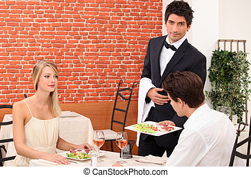 Waiter serving a young couple