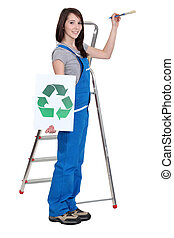lovely brunet painter in blue dungarees holding brush and...