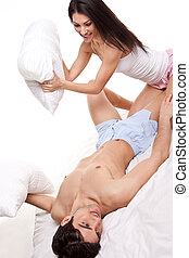 Couple Having Pillow Fight - Attractive young couple having...