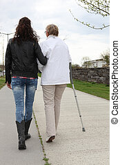 Young woman helping elderly lady walk
