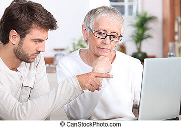 Young man showing a senior woman how to use a laptop