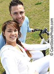 Young couple riding bikes in a park