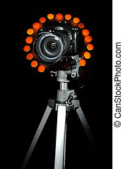 DSLR on a tripod isolated on black background with bokeh...