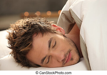 Handsome young man asleep in bed