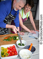 Senior couple preparing a meal searching for a recipe on internet
