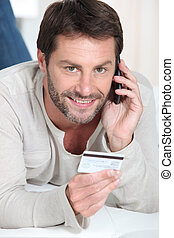 Man giving credit card number on the phone