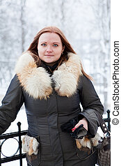 One caucasian female in winter clothes standing near rails.