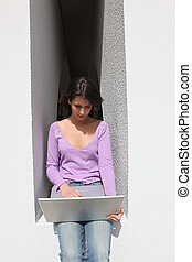 Woman in front of a laptop computer outdoors