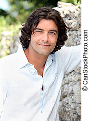 Handsome man with long hair standing by an old stone wall