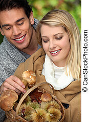 young couple with basket full of mushrooms and chestnuts