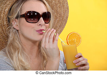 Woman drinking glass orange juice