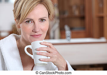 Blond woman in dressing gown drinking coffee