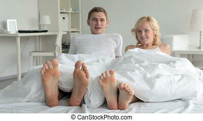 Playful couple in bed - Couple playfully moving feet